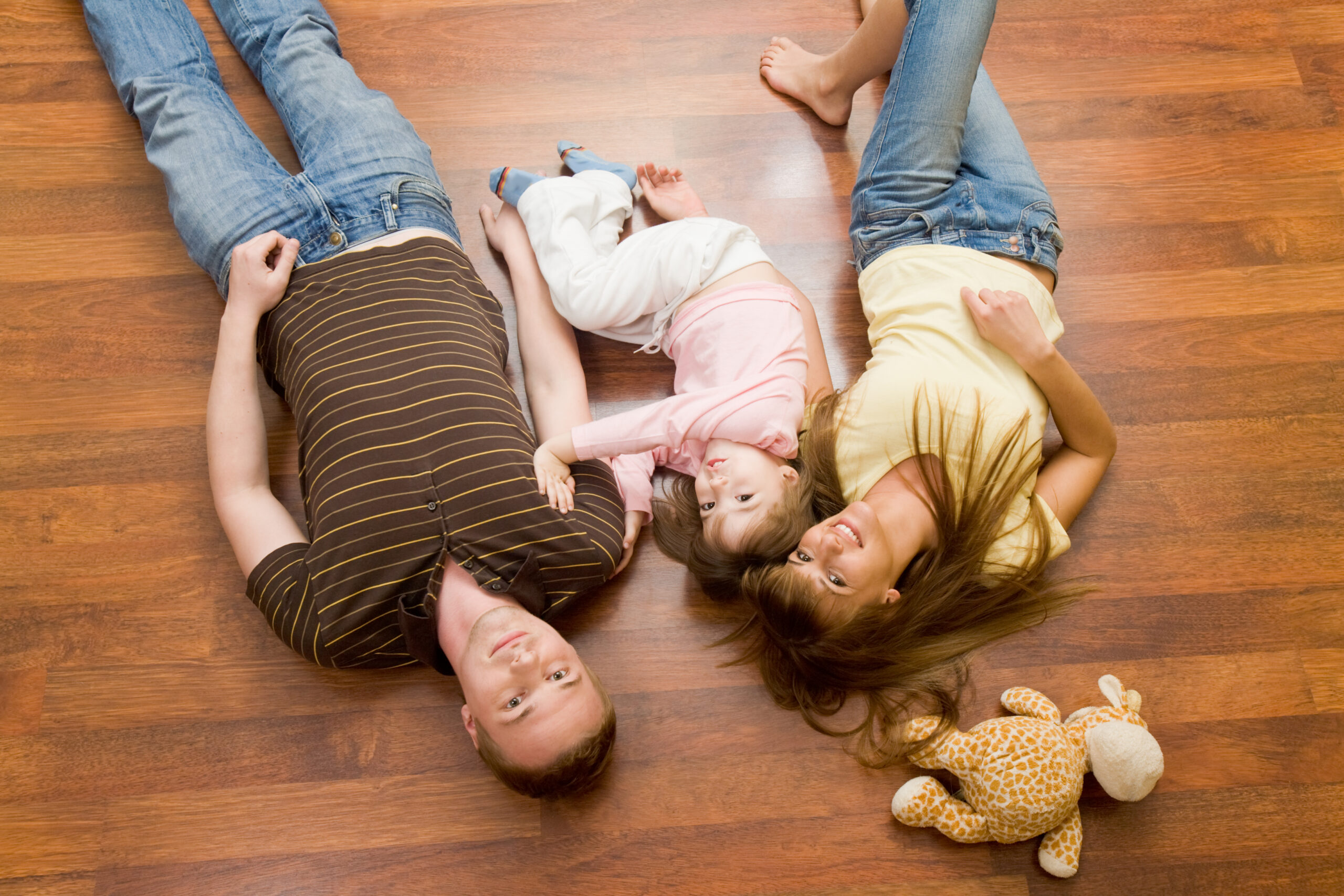 View from above of resting family lying on the floor and looking at camera